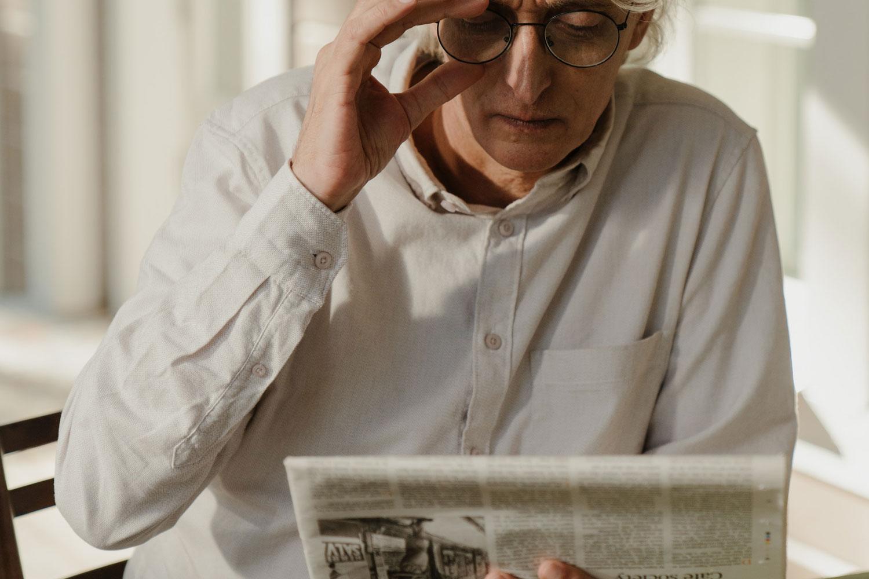 Older man looking at newspaper